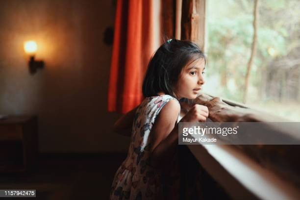 portrait of a preschool age girl looking through window - one girl only stock pictures, royalty-free photos & images