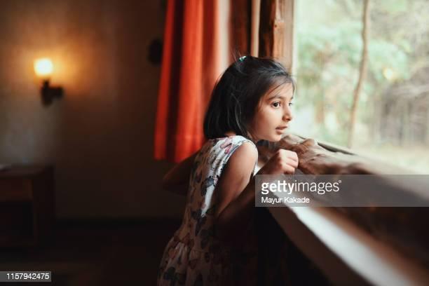 portrait of a preschool age girl looking through window - 少女一人 ストックフォトと画像