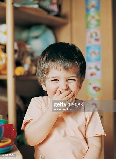 Portrait of a Preschool Girl Laughing With Her Hand Covering Her Mouth