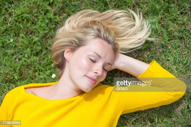 portrait of a pretty blond woman lying down in the park with closed eyes - lying down stock-fotos und bilder