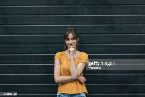 portrait of a pretty woman in front of roller shutter - roller shutter stock pictures, royalty-free photos & images