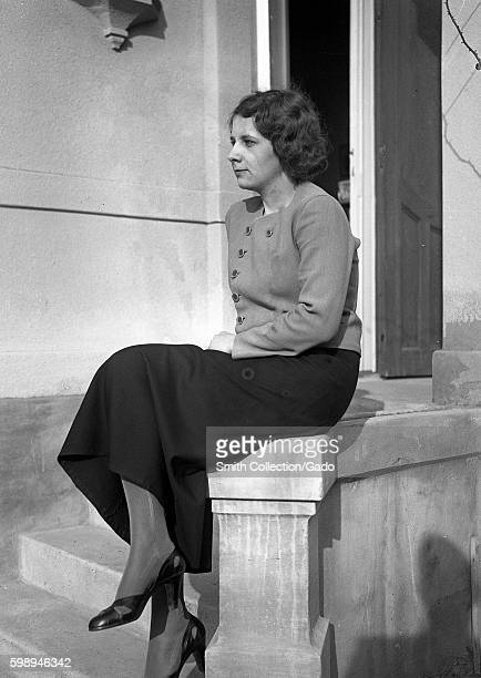 Portrait of a pretty, young woman wearing a buttoned blouse, long skirt, pantyhose and heels, sitting on the edge of a concrete stairway outdoors and...