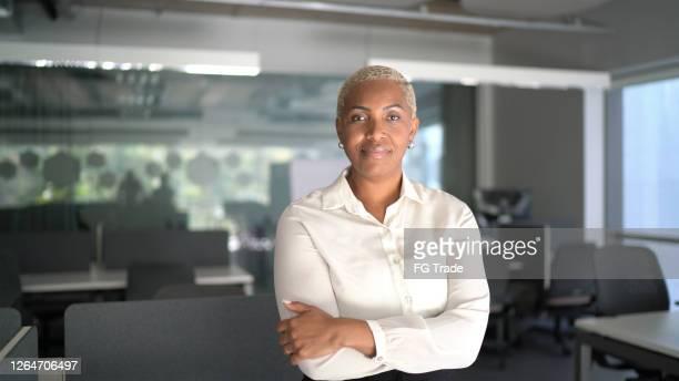 portret van een trots onderneemster die zich met wapens bevindt die in het bureau worden gekruist - oprichter stockfoto's en -beelden