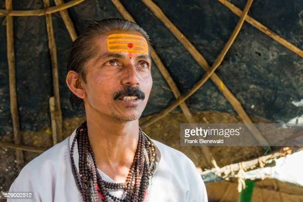 Portrait of a priest Brahmin working at the holy river Ganges at Dashashwamedh Ghat Main Ghat in the suburb Godowlia
