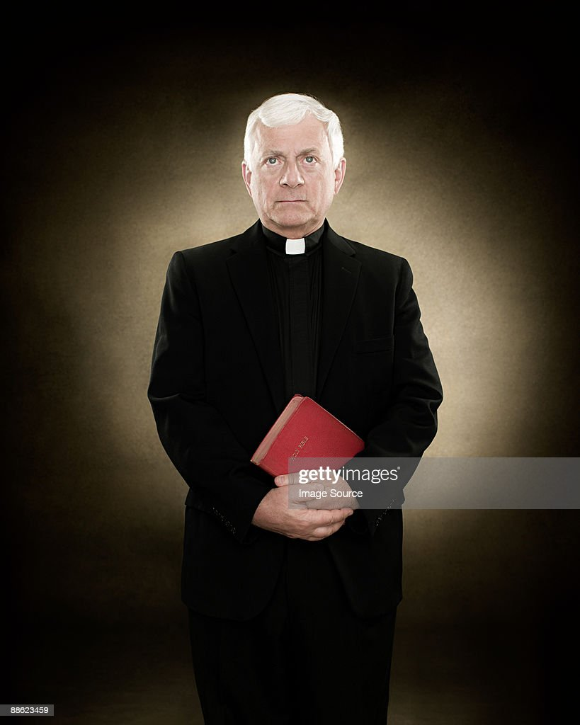 Portrait of a priest holding a bible : Stock Photo
