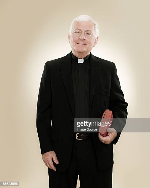 portrait of a priest holding a bible - priest stock pictures, royalty-free photos & images