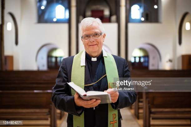 portrait of a priest in church reading the bible - pastor stock pictures, royalty-free photos & images