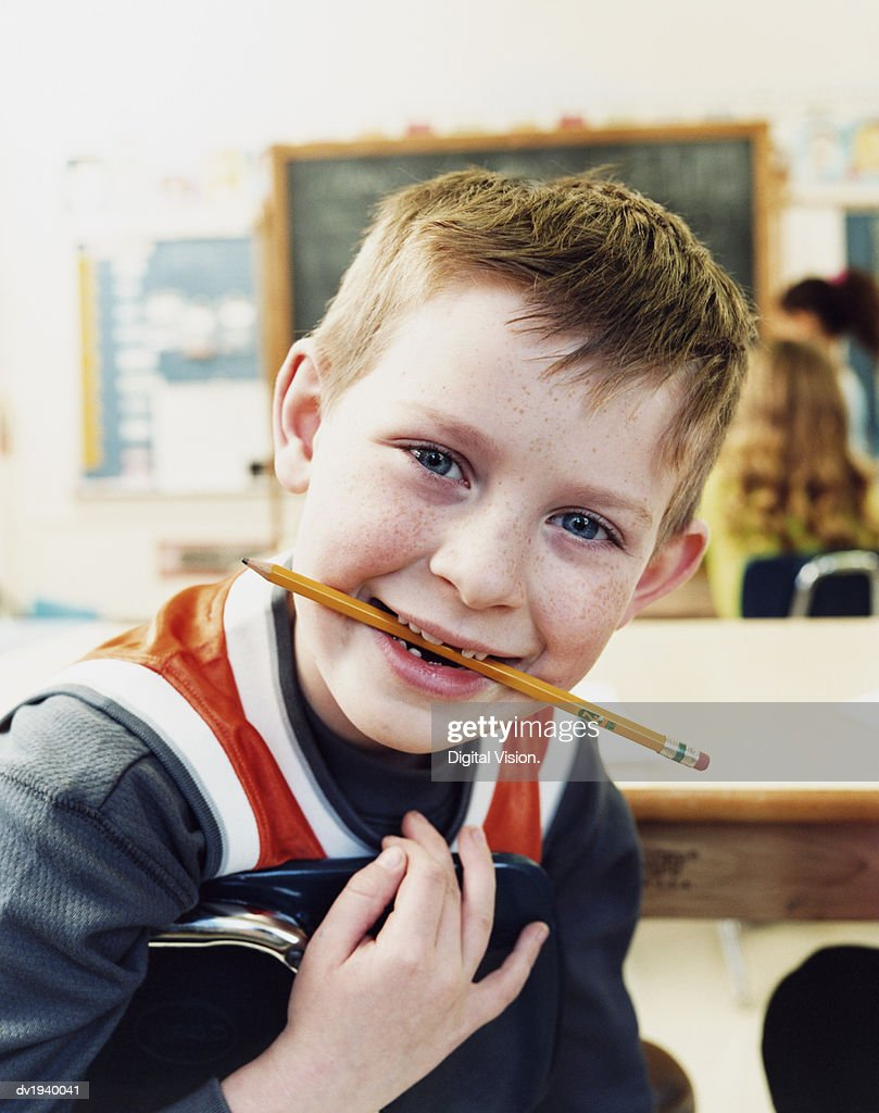 Portrait of a Primary School Boy Chewing a Pencil : Stock Photo