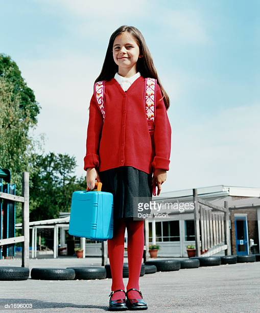Portrait of a Primary School Girl Standing Outside a Primary School Holding Her Lunchbox