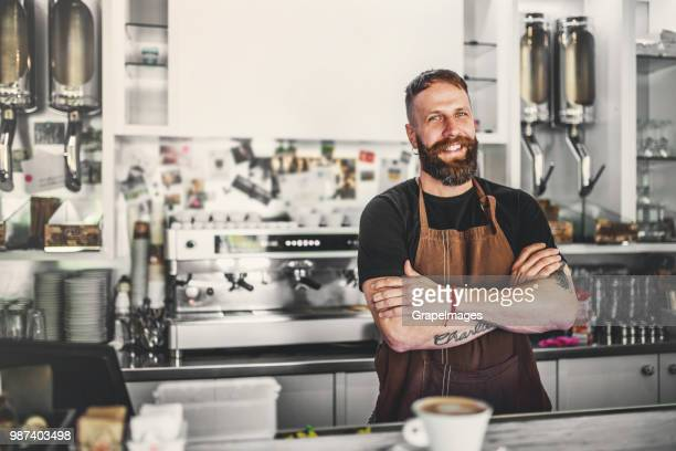 Portrait of a professional bearded barista behind a counter in a cafe, arms crossed.