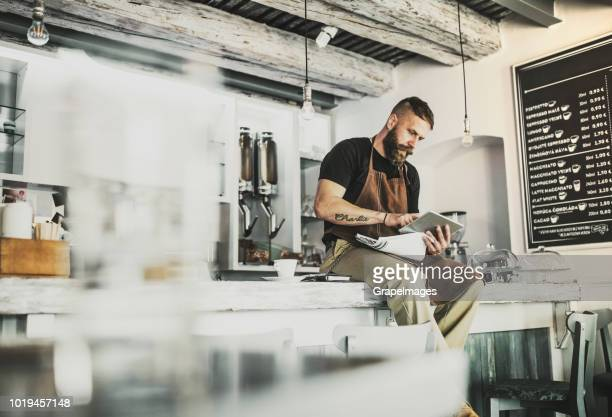 portrait of a professional bearded barista sitting on a counter in a cafe, using tablet. - freelance foto e immagini stock