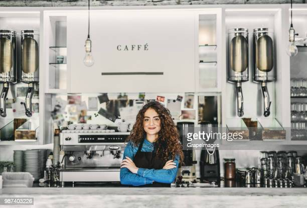 portrait of a professional young woman barista behind a counter in a cafe. - bar counter stock pictures, royalty-free photos & images