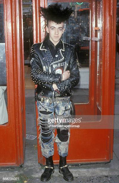 A portrait of a punk guy standing outside a phone box