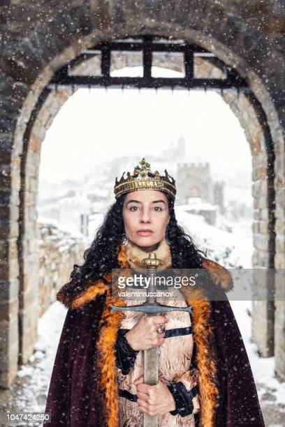 portrait of a queen in front of her castle, holding a sword - medieval queen crown stock pictures, royalty-free photos & images