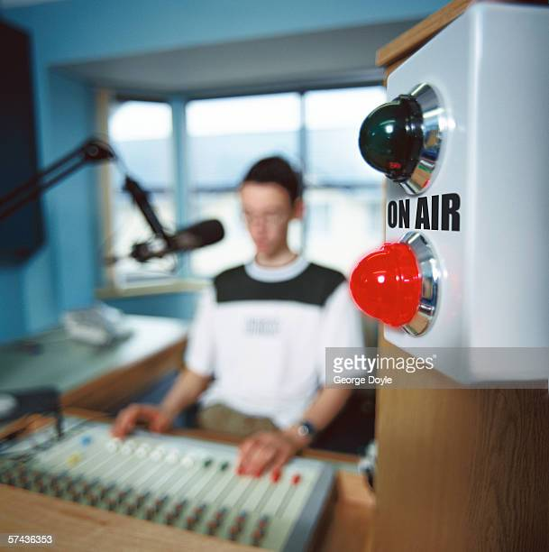 portrait of a radio jockey operating a sound mixer in a studio; blurred