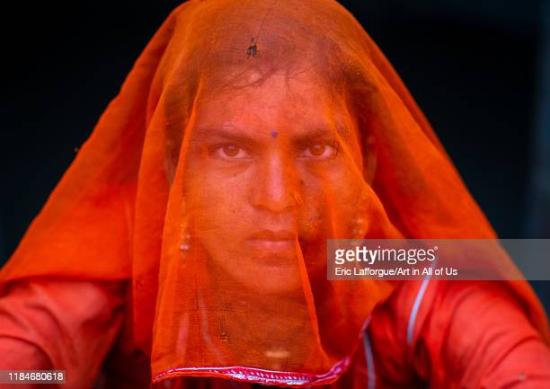 Portrait of a rajasthani woman hidding her face under a orange sari, Rajasthan, Jaisalmer, India on July 22, 2019 in Jaisalmer, India.