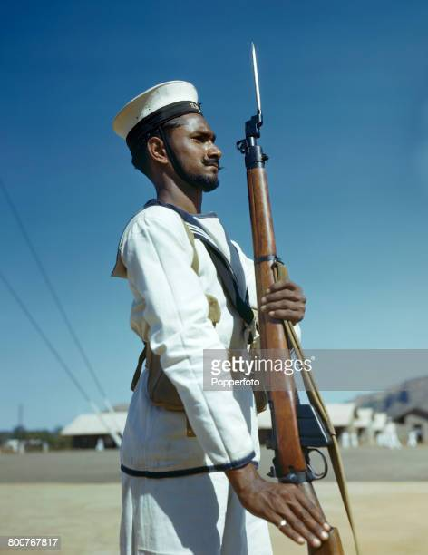 Portrait of a rating of the Royal Indian Navy pictured standing to attention holding a Short Magazine LeeEnfield rifle in India in February 1945