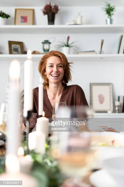 portrait of a readheaded woman sitting at a dinner party - redhead stock pictures, royalty-free photos & images