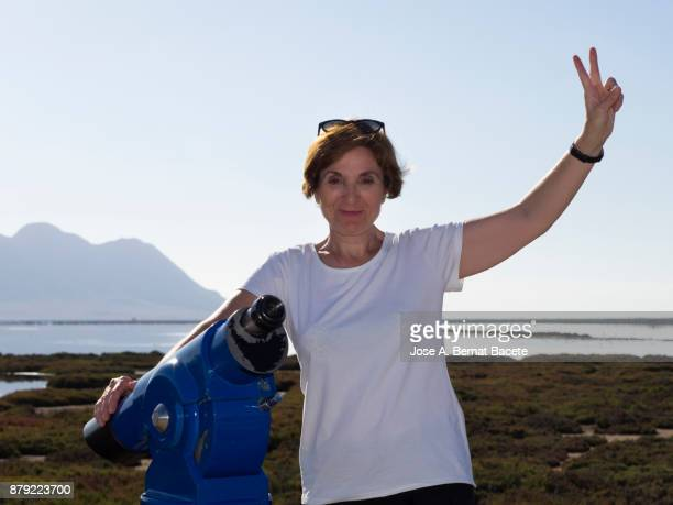 portrait of a real people woman of tourism, doing the sign of the victory outdoors in the nature looking at the camera. almeria, andalusia, spain. - iberian stock photos and pictures