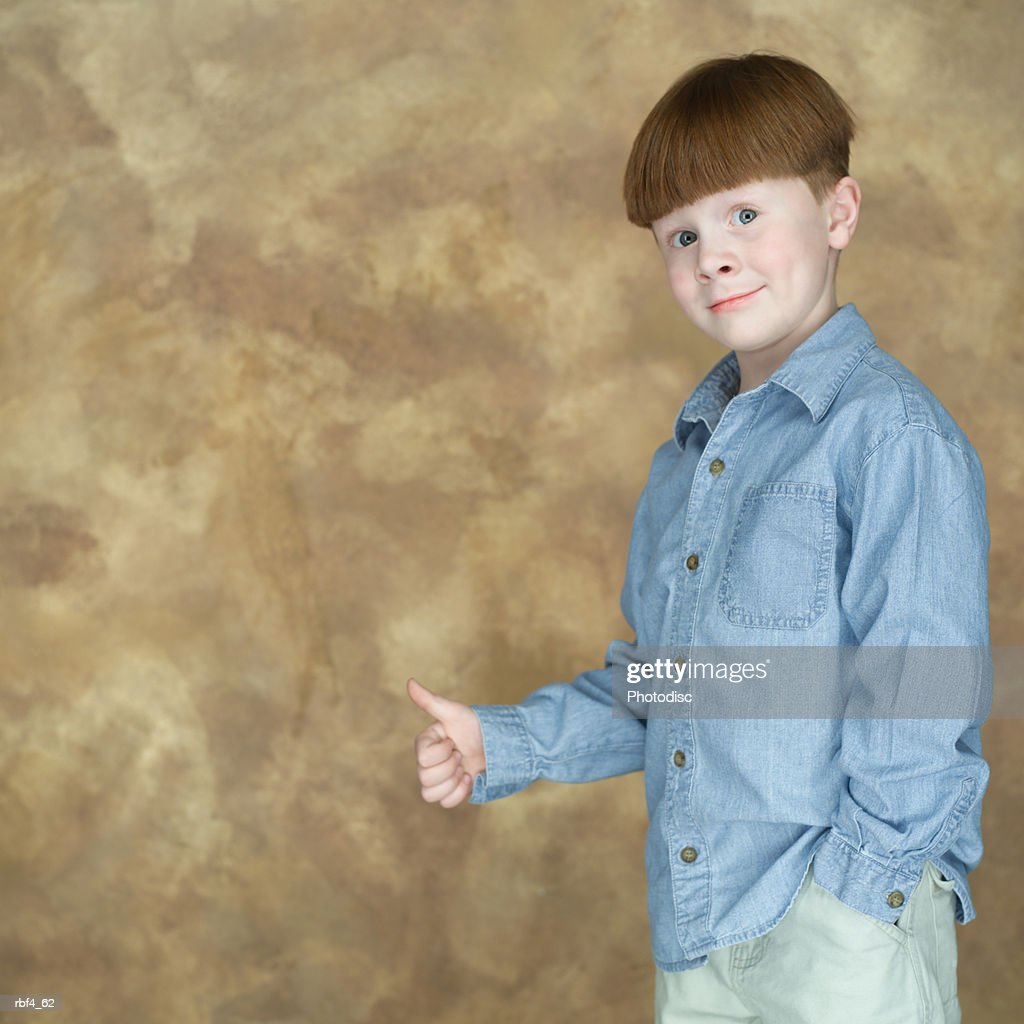 portrait of a redheaded caucasian boy in a blue shirt as he makes the tumbs up sign and smiles : Stockfoto