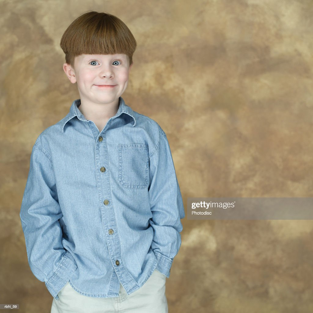 portrait of a redheaded caucasian boy in a blue shirt as he puts his hands in his pockets and smiles : Stockfoto