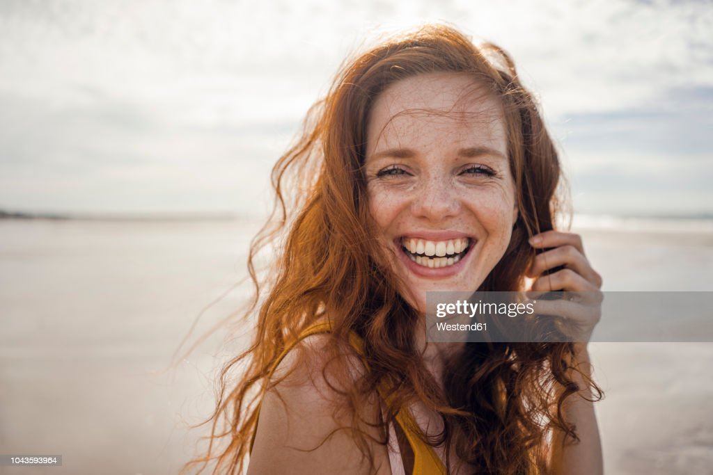 Portrait of a redheaded woman, laughing happily on the beach : Stockfoto