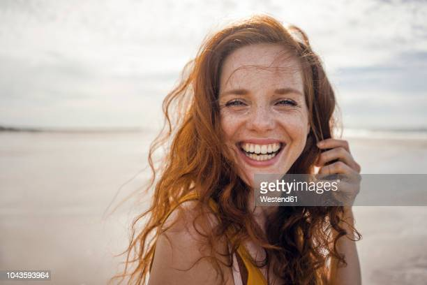 portrait of a redheaded woman, laughing happily on the beach - alegre fotografías e imágenes de stock