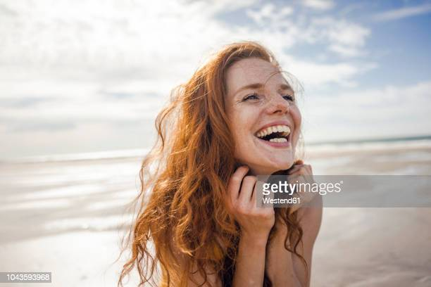 portrait of a redheaded woman, laughing happily on the beach - rotes haar stock-fotos und bilder