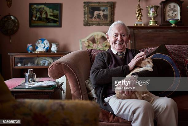 a portrait of a retired antique dealer and his cat - real people stock pictures, royalty-free photos & images