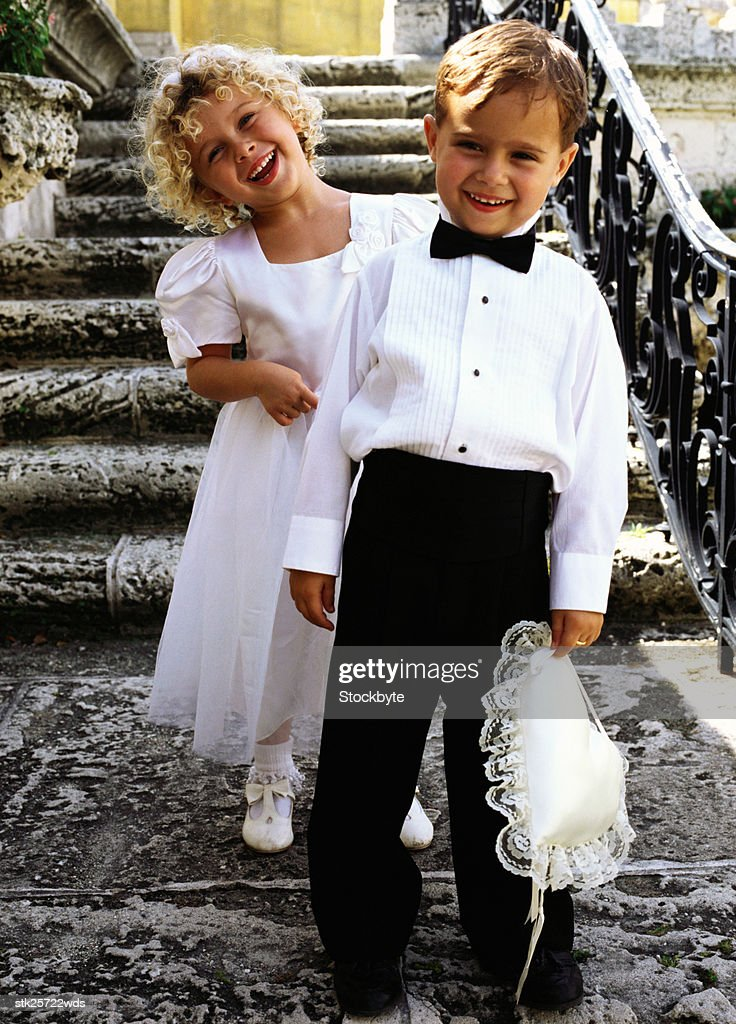 portrait of a ring bearer (6) and a bridesmaid (6) standing on the steps : Stock-Foto