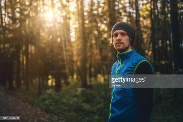 porträt eines läufers in einem park am sonnenuntergang - rennen körperliche aktivität stock-fotos und bilder