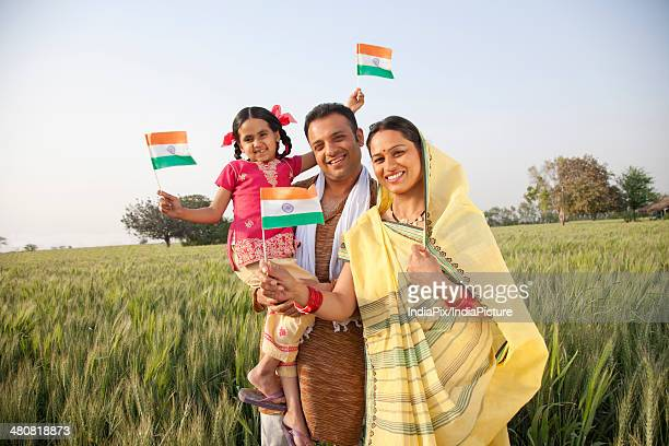 Portrait of a rural family holding an Indian flag in farm