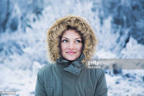 Portrait of a russian girl with beautiful eyes and covered with hairy hoodie of his winter coat in the frozen morning and frozen landscape in the Catalan Pyrenees.