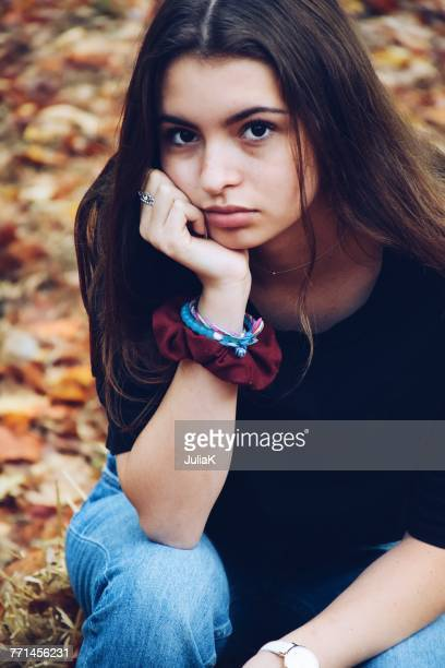 portrait of a sad teenage girl sitting in garden - one teenage girl only stock pictures, royalty-free photos & images