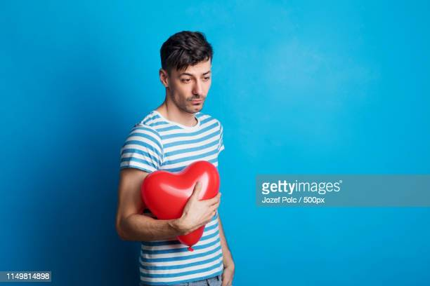 portrait of a sad young man in a studio on a blue background, holding red heart - ボーダーシャツ ストックフォトと画像
