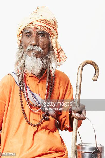 Portrait of a sadhu holding a cane and a utensil