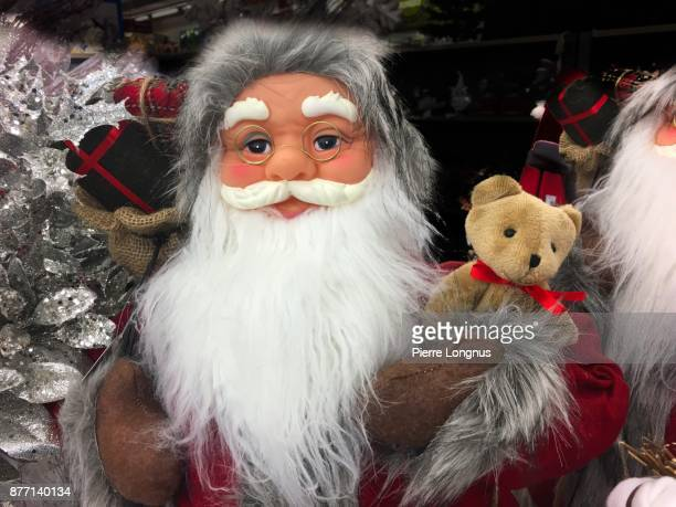 Portrait of a Santa Claus puppet in a store holding a teddy bear