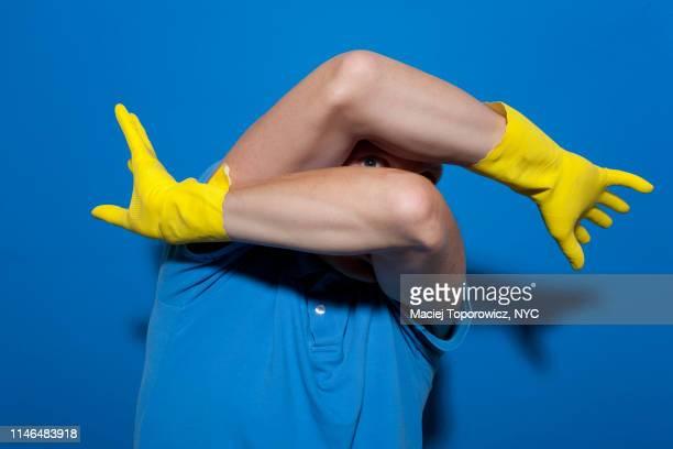 portrait of a scared man with shaved head wearing rubber gloves against blue background. - ansteckende krankheit stock-fotos und bilder