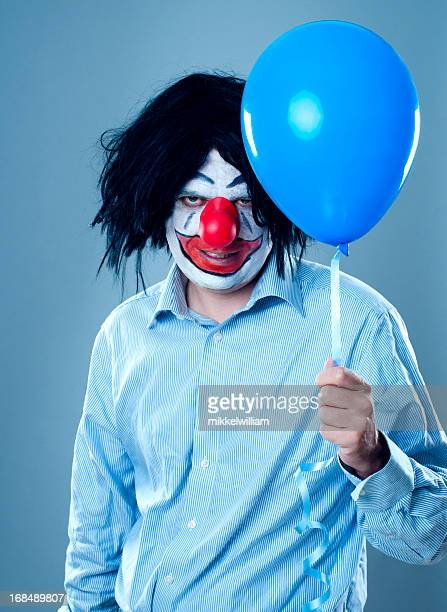 portrait of a scary clown with a blue balloon - scary clown makeup stock photos and pictures