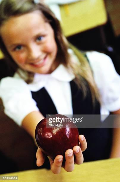 portrait of a school girl (8-10) holding out an apple - 10 11 jahre stock-fotos und bilder