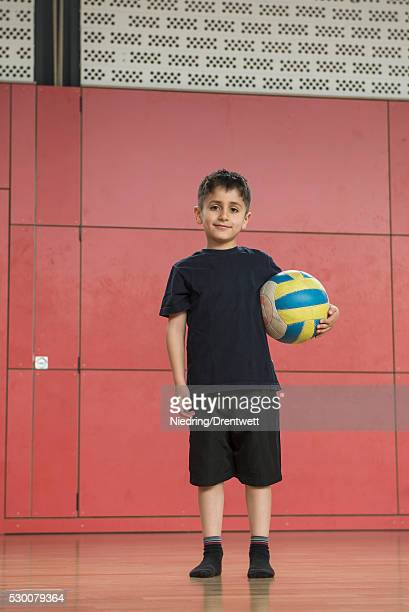 Portrait of a schoolboy holding a ball in sports hall of school, Munich, Bavaria, Germany