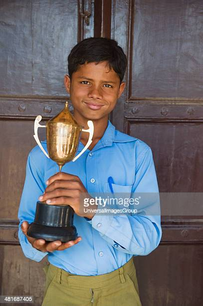 Portrait of a schoolboy holding a trophy