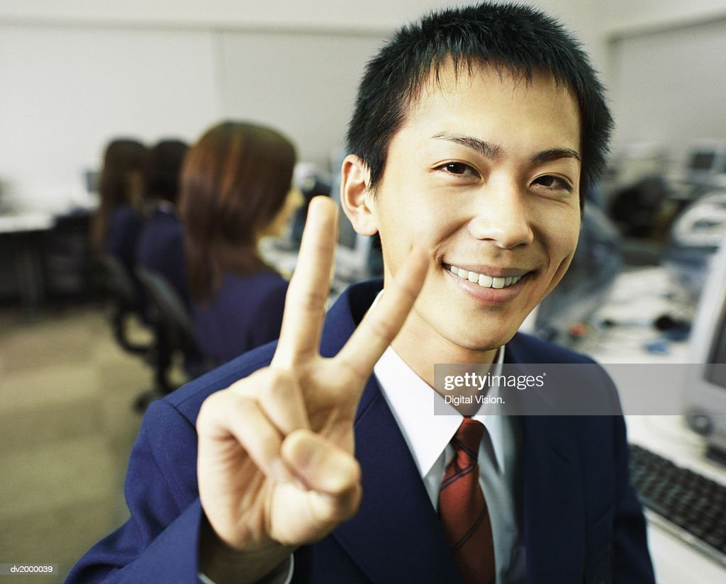 Portrait of a Schoolboy Making a Peace Sign, in a Computer Room : Stock Photo