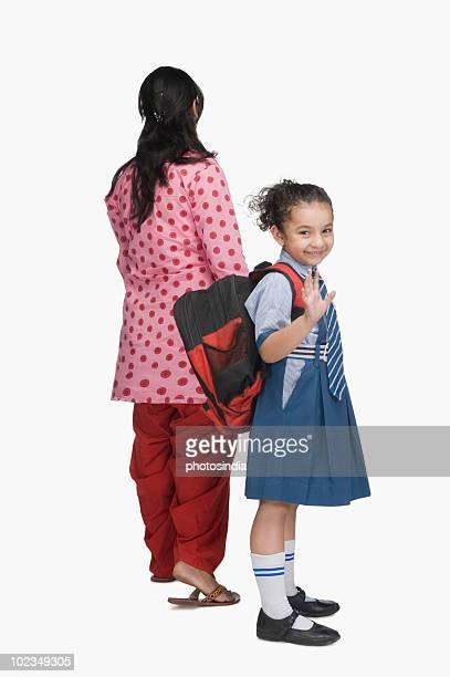 Portrait of a schoolgirl holding her mother's hand