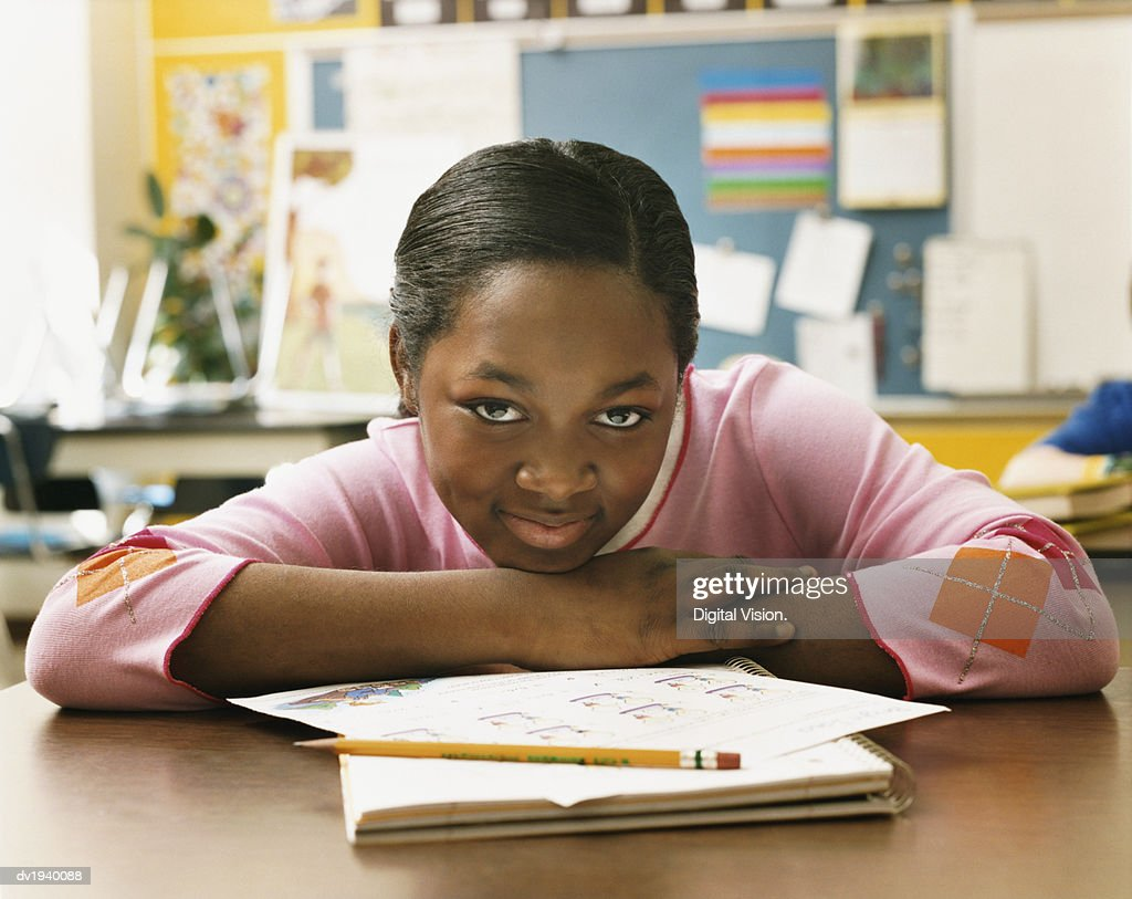 Portrait of a Schoolgirl Sitting at Her Desk in a Classroom : Stock Photo