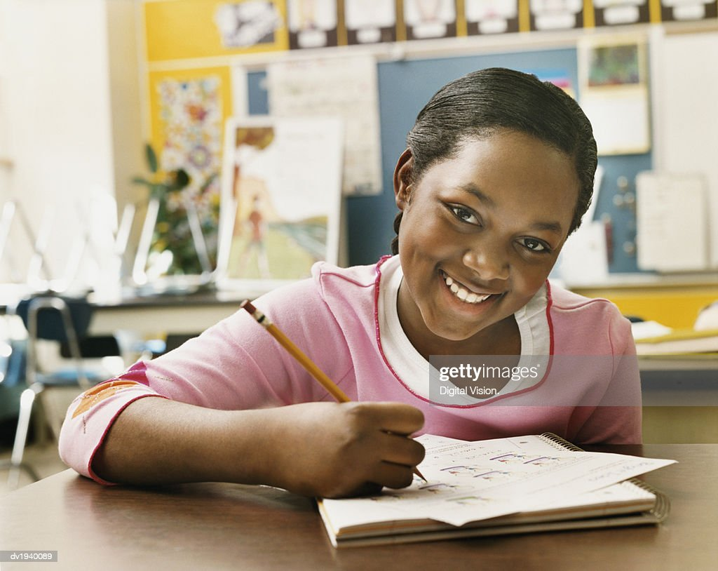 Portrait of a Schoolgirl Writing in Her Exercise Book in a Classroom : Stock Photo