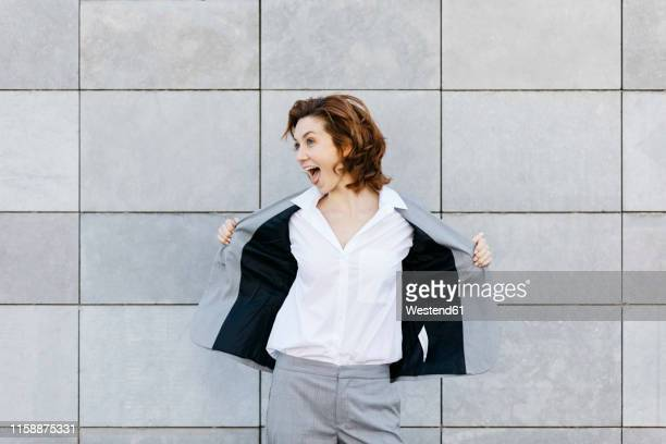 portrait of a screaming young businesswoman in front of wall with gray tiles, opening her jacket - coat fotografías e imágenes de stock