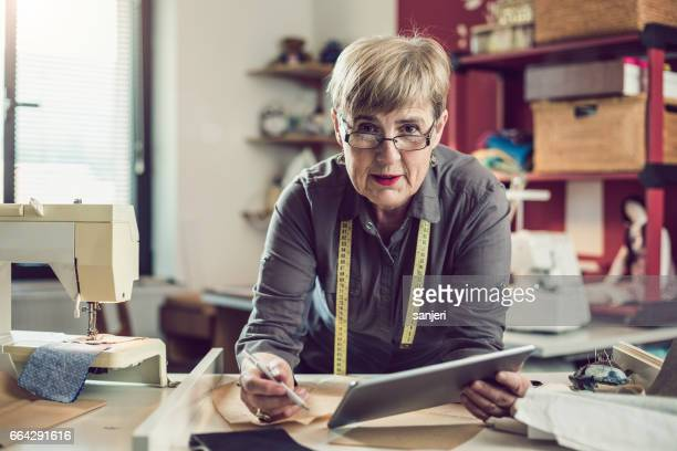 portrait of a seamstress beside a sewing machine and using a digital tablet - needlecraft stock pictures, royalty-free photos & images