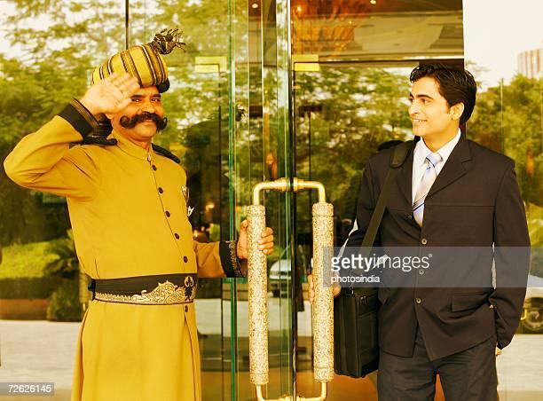 Portrait of a security guard saluting a businessman