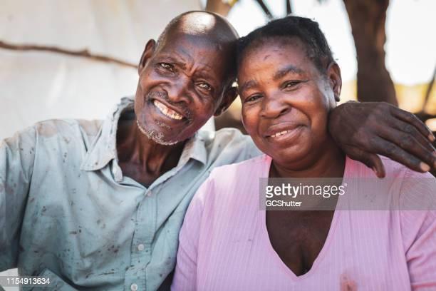 村の彼らの小屋の近くに座っているシニアアフリカのカップルの肖像 - ザンビア ストックフォトと画像